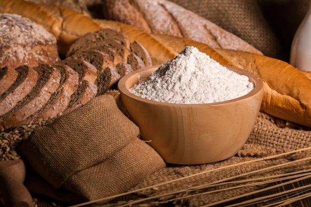 Pain de blé entier, farine et sac en tissu sur une table en bois. Photo Premium