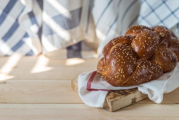 Pain à challah ou pain juif traditionnel sur une plaque de bois sur une table en bois Photo Premium