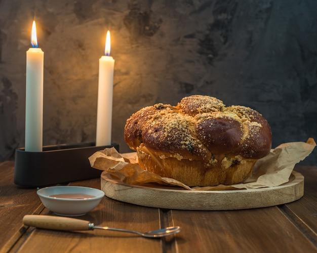 Pain challah sucré sur une assiette ronde boisée sur une table en bois marron avec du miel et deux bougies le soir du shabbat, rendant kidush Photo Premium