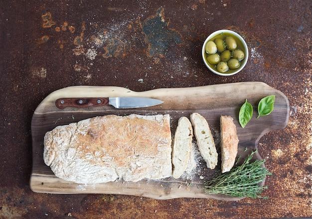 Pain ciabatta fait maison avec olives, basilic et thym sur une planche en bois de noyer sur métal rouillé grunge, vue de dessus Photo Premium