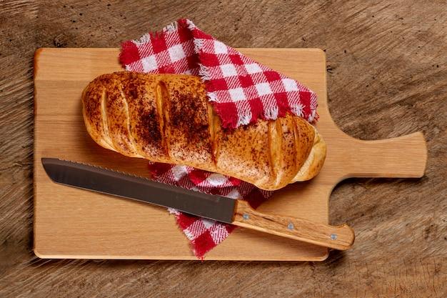 Pain et couteau sur planche de bois Photo gratuit