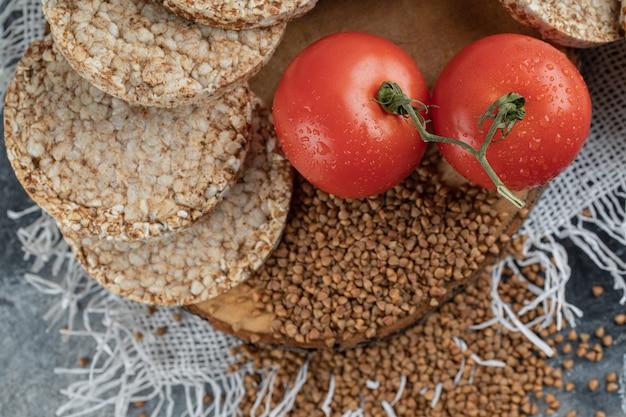 Pain Croustillant Soufflé, Tomates Et Sarrasin Cru Sur Une Surface En Marbre Photo gratuit