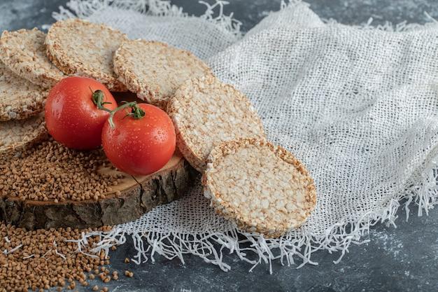 Pain Croustillant, Tomates Et Sarrasin Cru Sur Morceau De Bois Photo gratuit