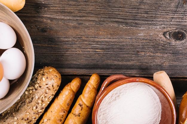 Pain cuit au four; farine et oeufs dans un bol sur un fond texturé en bois Photo gratuit