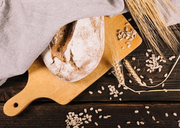 Pain et épi de blé avec des graines de tournesol sur une table en bois foncée Photo gratuit