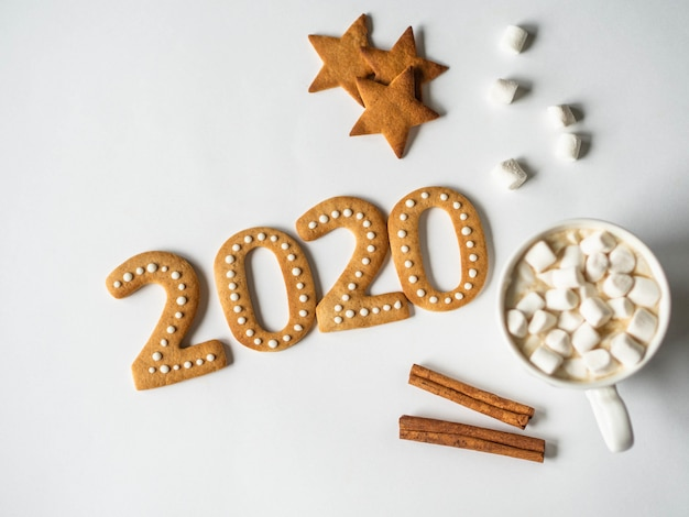 Pain d'épice 2020 biscuits au gingembre et mug au chocolat avec guimauves Photo Premium