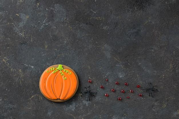 Pain d'épice sous la forme d'une citrouille à la main et deux araignées noires Photo Premium