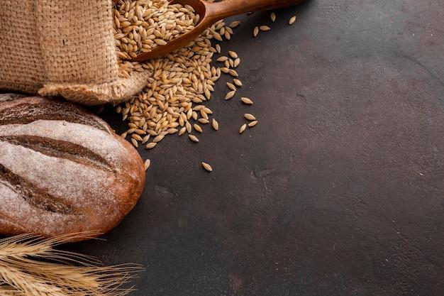 Pain et graines de blé dans un sac de jute Photo gratuit