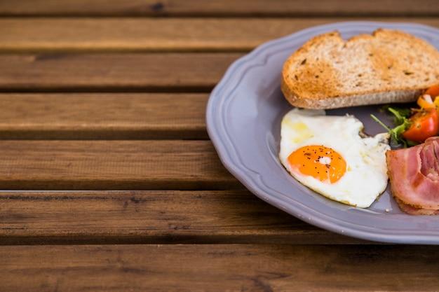 Pain grillé; oeuf frit; bacon sur une assiette en céramique grise sur la table en bois Photo gratuit