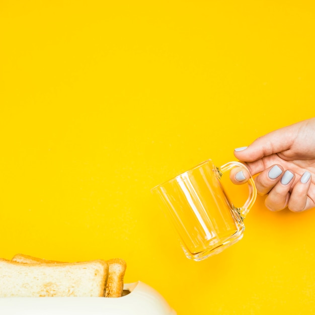 Le pain grillé sort du grille-pain sur un fond jaune Photo Premium