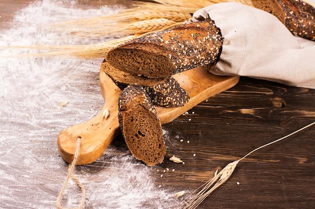 Pain maison au sésame et aux graines de pavot sur une table en bois. Photo Premium