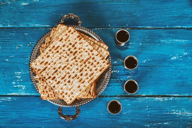 Un pain de matza juif avec quatre verres de vin. concept de vacances pascal Photo Premium