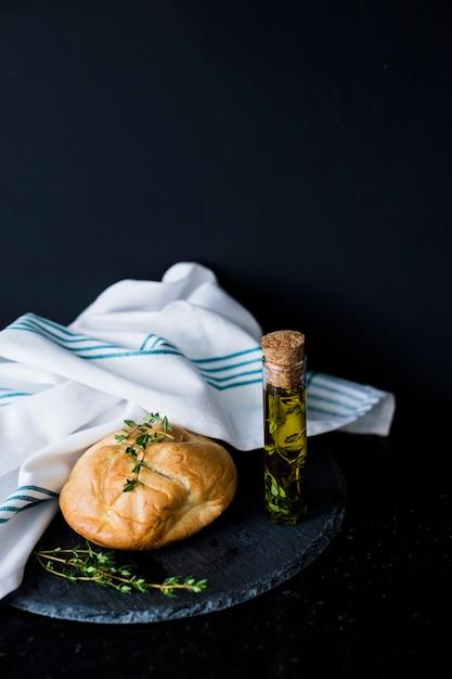 Pain de pain; le thym; huile d'olive et serviette blanche sur ardoise sur fond noir Photo gratuit