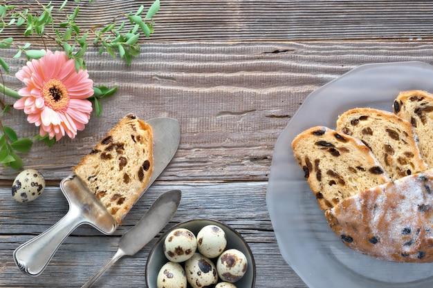 Pain de pâques (osterbrot en allemand). vue de dessus du pain fruité traditionnel sur du bois rustique avec des feuilles fraîches et des oeufs de caille. Photo Premium