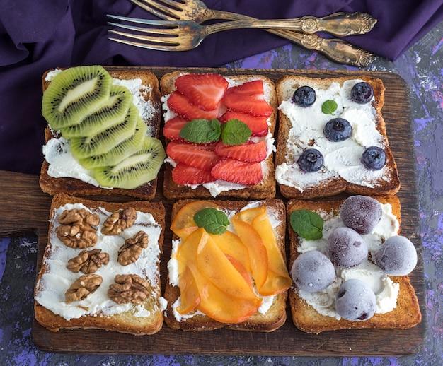 Pain perdu avec du fromage à pâte molle, des fraises, du kiwi, des noix de grenoble, des cerises et des bleuets Photo Premium