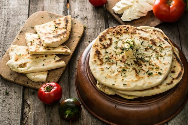 Pain pita sur planche de bois avec fromage feta, tomates et poivrons. nature morte de nourriture. g Photo Premium