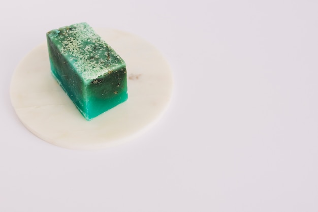 Pain de savon vert sur un panneau circulaire sur une surface blanche Photo gratuit