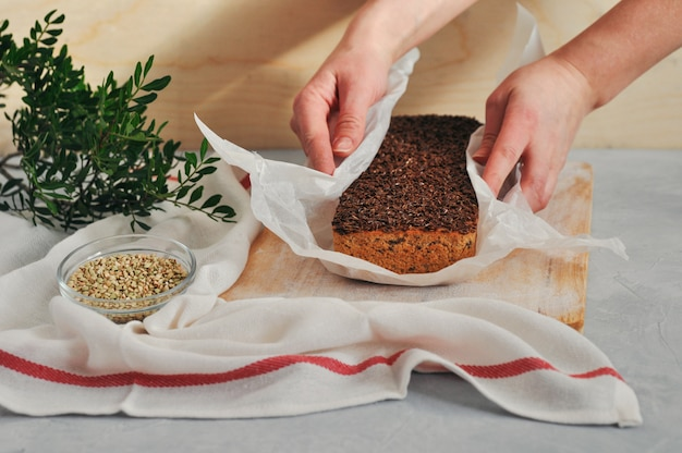 Pain végétalien fait maison sur un levain de sarrasin vert avec des graines de lin, tournesol dans les mains des femmes sur un fond en bois. nutrition saine et appropriée. Photo Premium