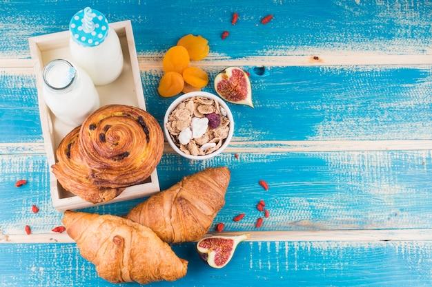 Pains cuits au four avec des bouteilles de lait dans un plateau près des abricots secs; figue; et flocons de maïs sur fond en bois bleu Photo gratuit