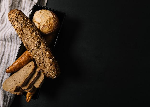 Pains à grains entiers cuits au four sur fond noir foncé Photo gratuit