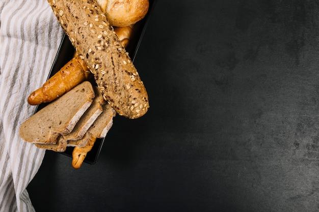 Pains à grains entiers cuits au four avec serviette sur le plan de travail noir Photo gratuit