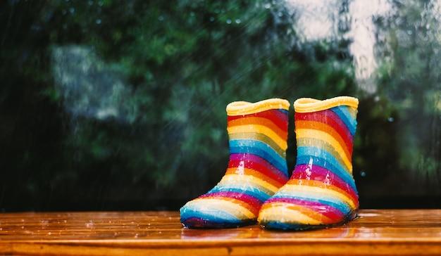 Paire de bottes de pluie arc-en-ciel assis à l'extérieur avec un arrière-plan flou Photo Premium