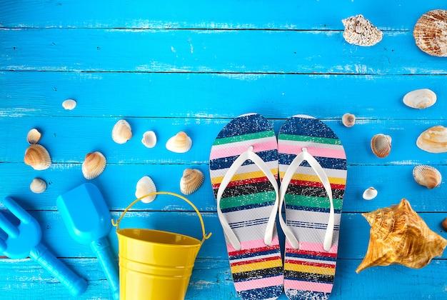 Paire de chaussons de plage, d'un seau pour bébé jaune et de coquillages Photo Premium