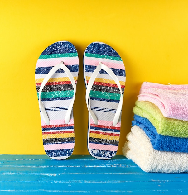 Paire de chaussons de plage et serviettes sur fond bleu et jaune Photo Premium