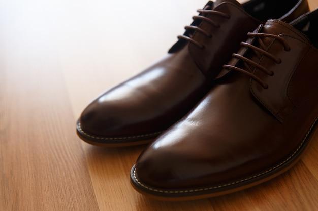 Une paire de chaussures en cuir marron sur un plancher en bois Photo Premium