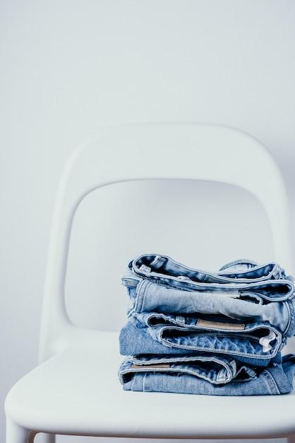 Paire de jeans sur une chaise blanche sur fond blanc Photo Premium