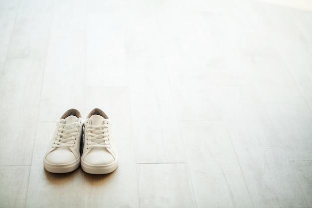 Paire de nouvelles baskets blanches élégantes sur un plancher en bois. Photo Premium