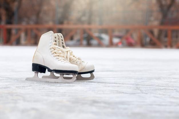 Une Paire De Patins à Glace Blancs Se Tient Sur Une Patinoire Ouverte. Sport D'hiver Photo Premium