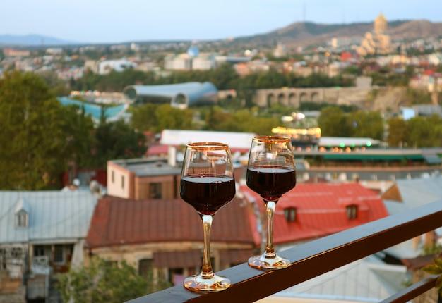Paire de verres à vin sur le balcon avec vue aérienne sur la ville en toile de fond Photo Premium
