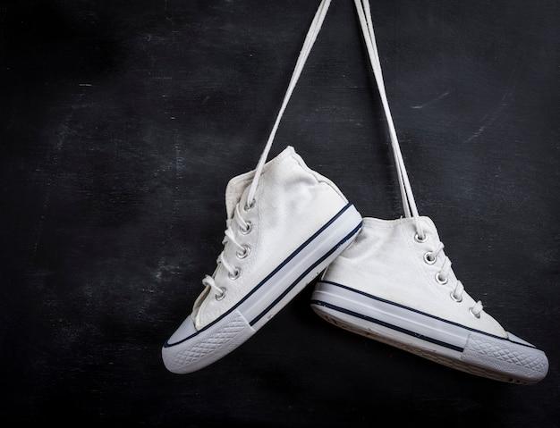 Des paires de chaussures textiles usagées pendent sur du noir Photo Premium