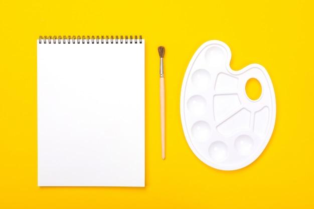 Palette d'art plastique avec album à peindre et pinceau sur fond orange Photo Premium