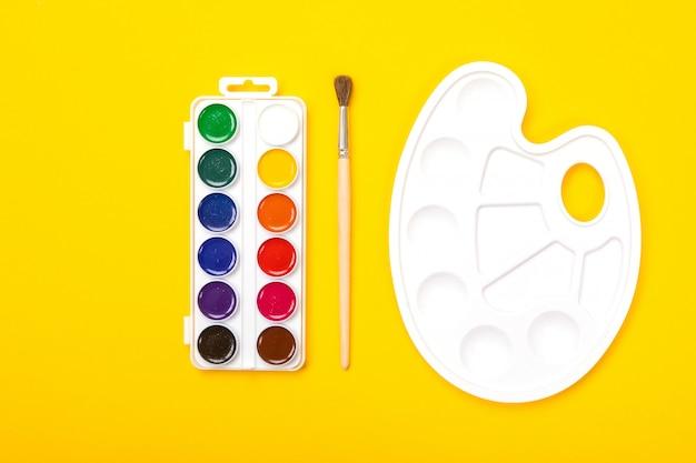 Palette d'art plastique avec aquarelle et pinceau sur fond orange Photo Premium