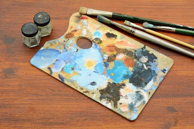 Palette de l'artiste avec des traits de peinture à l'huile colorés et des pinceaux Photo Premium