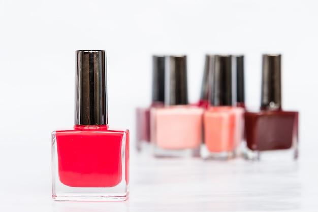 Une palette de bouteilles de vernis à ongles sur fond blanc Photo Premium