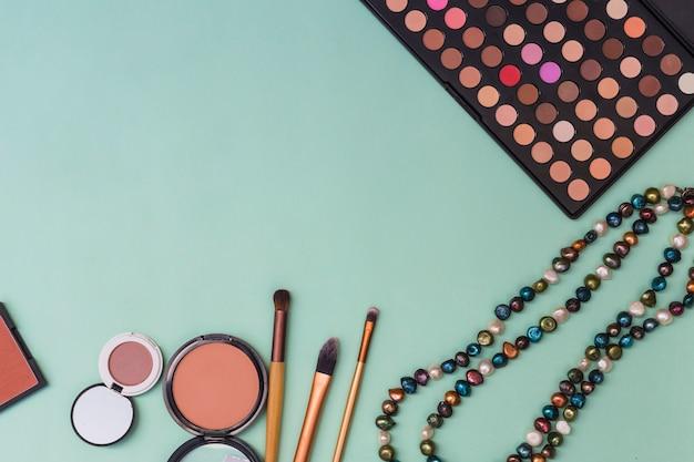 Palette de fard à paupières; collier de perles; fard à joues avec des pinceaux de maquillage sur fond pastel Photo gratuit