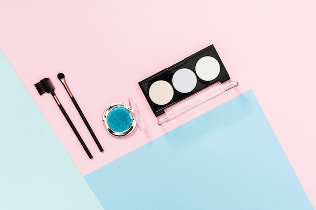 Palette d'ombres à paupières avec pinceau de maquillage sur fond coloré Photo gratuit