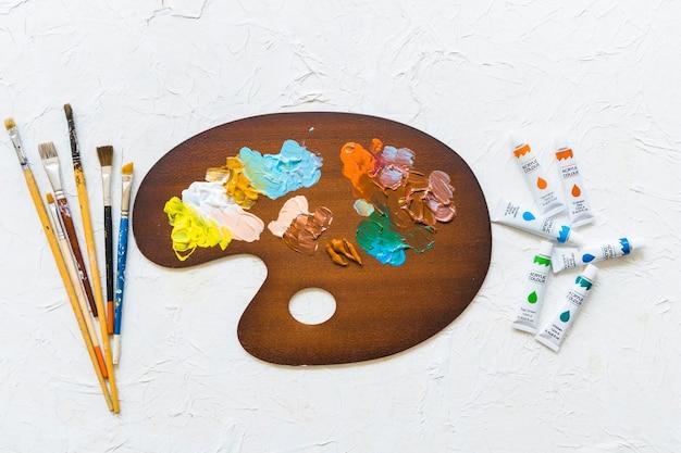 Palette De Peinture Vue De Dessus A Cote Des Pinceaux Et De La Peinture Photo Gratuite