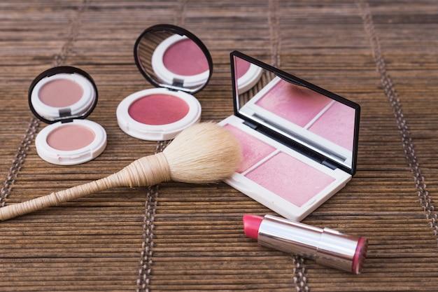 Palettes de fard à joues et rouge à lèvres rose avec pinceau de maquillage sur napperon Photo gratuit
