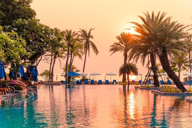 Palmiers Avec Parasols Et Chaises Au Bord De La Piscine Dans Un Hôtel De Luxe Au Lever Du Soleil Photo Premium