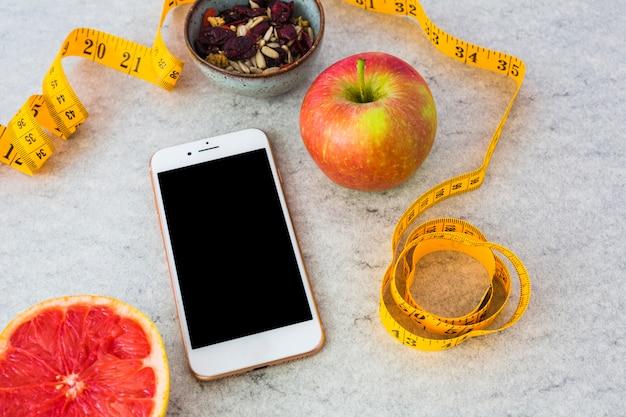 Pamplemousse coupé en deux; fruits secs; pomme; ruban à mesurer et smartphone sur fond gris Photo gratuit