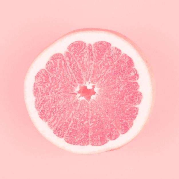 Pamplemousse frais juteux coupées en deux sur fond rose Photo gratuit