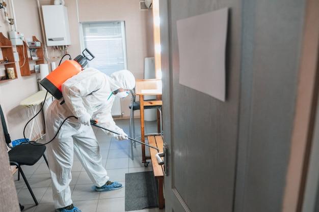 Pandémie De Coronavirus. Désinfecteur Dans Un Vêtement De Protection Et Un Masque Vaporise Des Désinfectants à La Maison Ou Au Bureau Photo gratuit