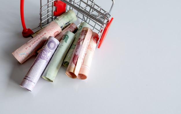 Panier D'achat Avec L'argent (argent Thaïlandais) à L'intérieur Est à L'envers Sur Blanc. Vue De Dessus Photo Premium