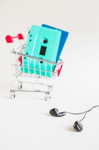 Panier d'achat avec des cassettes et des écouteurs noirs sur fond blanc Photo gratuit