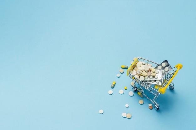 Panier D'achat Du Supermarché Plein De Pilules Sur Fond Bleu. Achats De Préparations Médicales, Achat Sur Internet. Mise à Plat, Vue De Dessus. Photo Premium