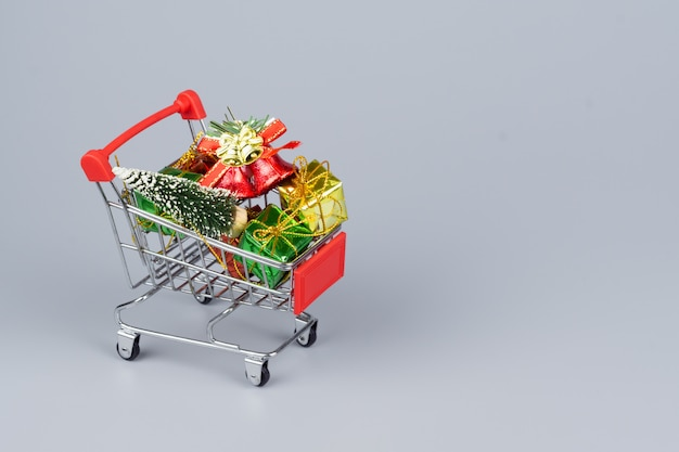 Panier d'achat avec des sapins de noël et des coffrets cadeaux miniatures sur fond gris Photo Premium